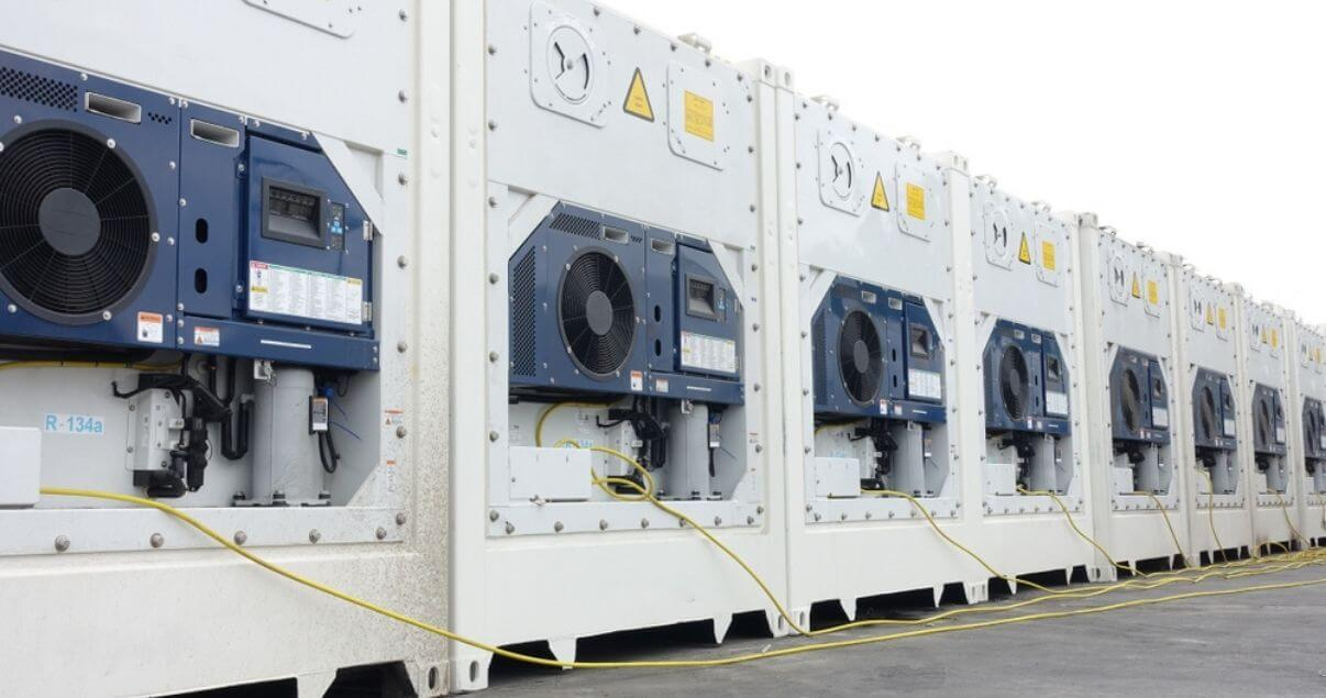 Fila de contenedores reefer listos para el transporte internacional de mercadería refrigerada